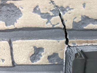 窓枠上部のサイディングのひび割れ