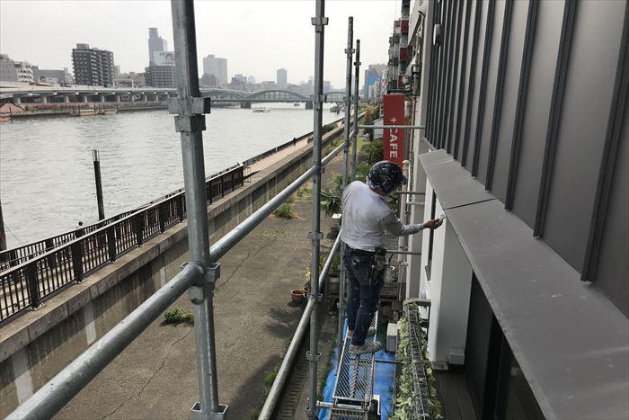 隅田川を背に塗装作業